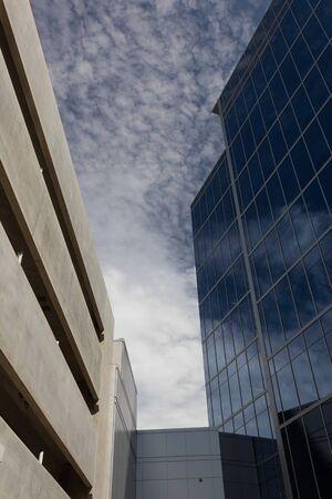 Blue sky reflected in a modern glass building opposite a stucco parking garage, vertical aspect Reklamní fotografie