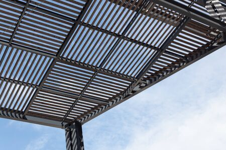 Gridded architectural shade structure of wood slats on a metal frame, blue sky with clouds, horizontal aspect