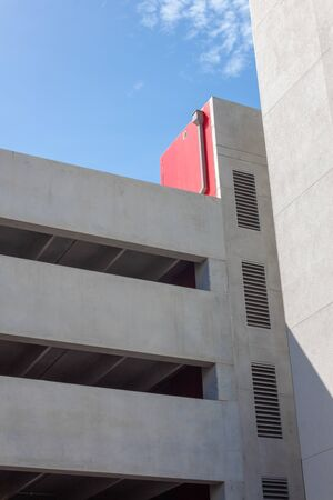 Modern architecture stucco parking garage, sunny day with blue sky, vertical aspect