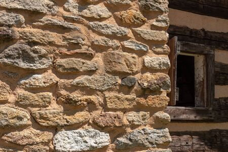 Crumbling stone wall of a building with open window in shadows, creative copy space, horizontal aspect