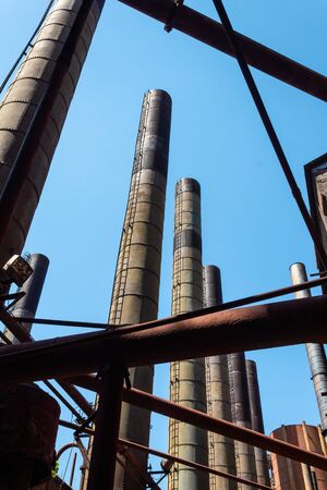 Lines of smokestacks, pipes, and girders silhouetted against a blue sky, old industrial complex, vertical aspect