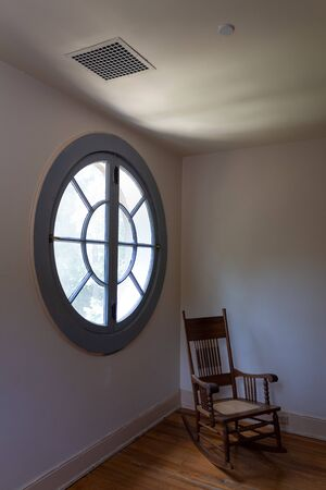 Large circular round window seen from interior, empty rocking chair, metaphor for aging, loss, death and grief, vertical aspect