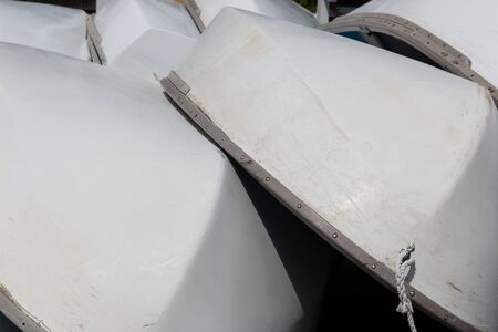 Stacked small sailboats, white hulls with metal trim, horizontal aspect