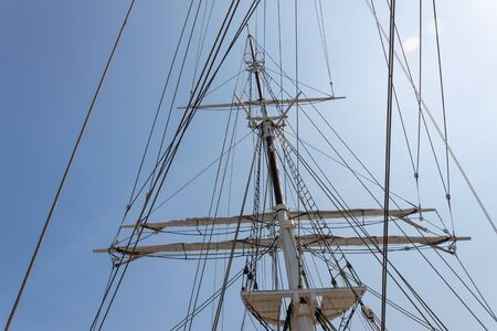 Tall ship mast and rigging in morning sun against a blue sky, horizontal aspect