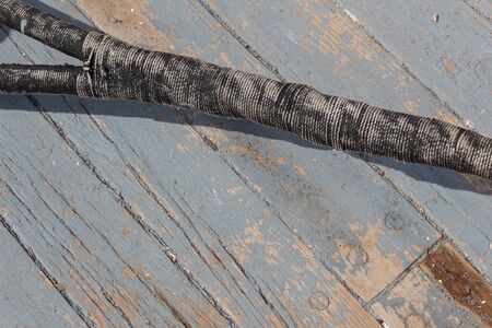 Old ship rope, wrapped splice joint, against a weathered wood and grey paint boat deck, horizontal aspect