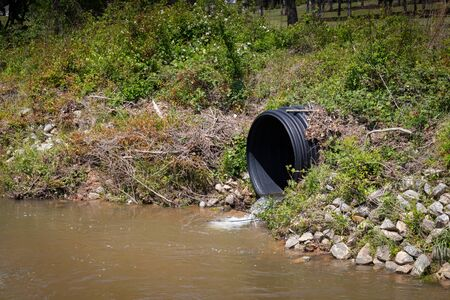Black plastic drainage culvert pipe releasing water into a stream, environmental safety issue, horizontal aspect