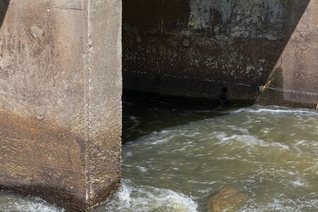 Rapidly moving water rushing around concrete bridge pilings, horizontal aspect Standard-Bild