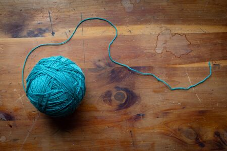 Ball of colorful aqua spun wool yarn with trailing string on a vintage wood table top, creative copy space, horizontal aspect Reklamní fotografie