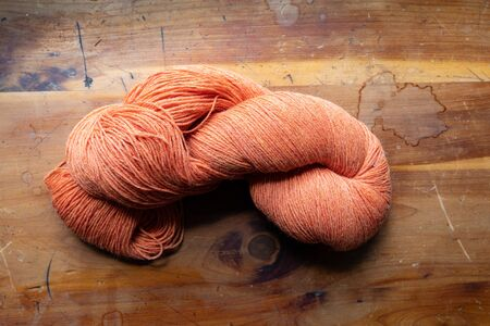 Skein of beautiful orange knitting yarn, rich color on an old wood table top, horizontal aspect