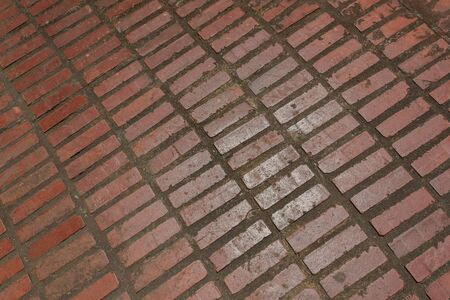 Background of red brick receding into a corner, glazed surface with thick mortar, horizontal aspect