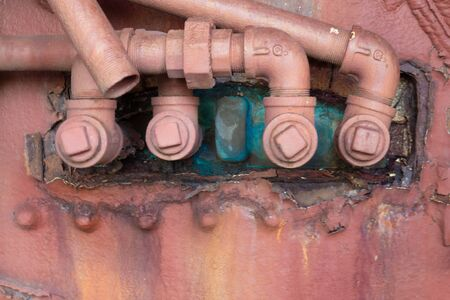 Close view of pipes and fittings, colorful verdigris copper patina and extremely heavy peeling paint, copy space, horizontal aspect