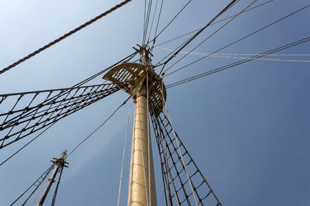 Extreme upward view of a tall ship mast, shrouds and rigging lines radiating out before blue sky, nautical theme, horizontal aspect