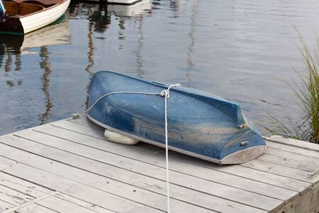 Blue hull of a small boat, upside down, lashed down to the top of a dock beside water, horizontal aspect