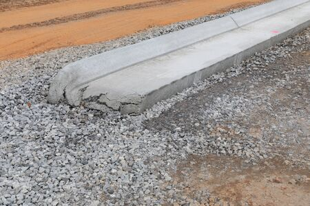 Cracked end of a section of extruded curb in gravel, road construction site, horizontal aspect