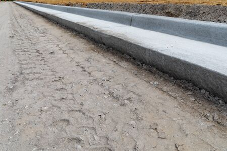 Diagonal view of fresh extruded curbing on a road construction site, dirt street bed, horizontal aspect