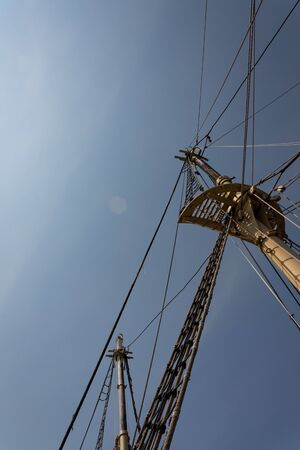 Extreme upward view of masts and rigging structures of an old sailing vessel, vertical aspect Archivio Fotografico