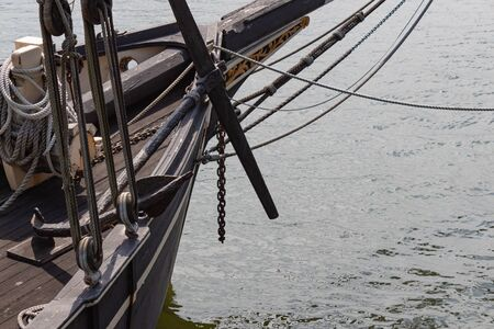 Old anchor and bowsprit of a vintage tall ship sailing vessel on the water, creative copy space, horizontal aspect