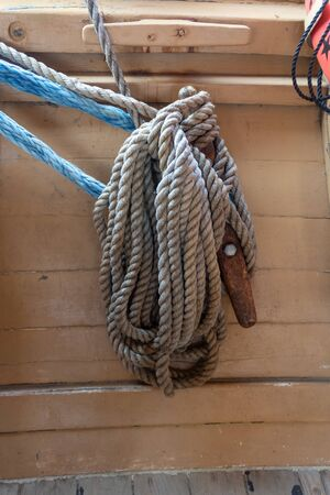 Old ropes coiled around a rusted metal cleat on an old fishing boat, vertical aspect