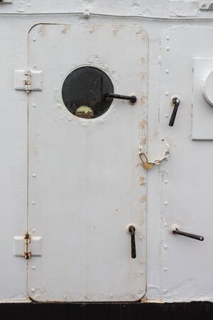 Ship door painted white with round porthole window, chained and padlocked, creative copy space, entry denied, vertical aspect Stockfoto