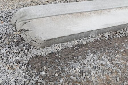 Closeup view of the end of a section of extruded concrete curbing on a bed of heavy gravel, new road construction, creative copy space, horizontal aspect Stock Photo