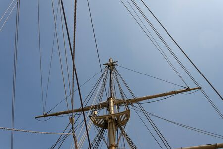 Top of mast on a vintage sailing vessel with ropes, lines, and shrouds against a blue sky, horizontal aspect