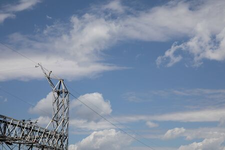 Metal truss structure of an electrical power substation against a dramatic blue sky with white clouds, creative copy space, horizontal aspect