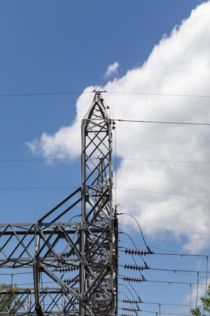 Tall metal trusses carrying electrical power lines and strain insulators silhouetted against a blue sky with dramatic white clouds, vertical aspect