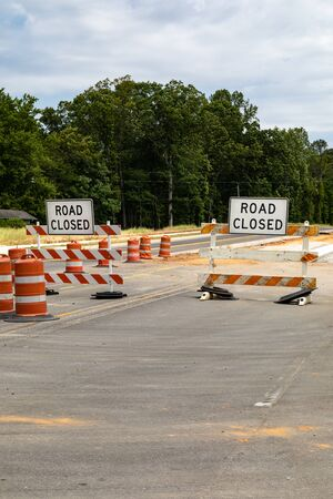 Road closed signs on traffic barricades, orange and white reflective barrels, asphalt copy space, vertical aspect
