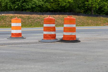 Three traffic barrels in a road construction area, orange safety barricade, asphalt copy space, horizontal aspect