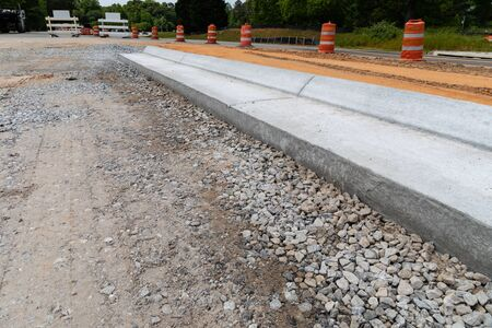 Traffic barricades alongside a new street under construction, gravel road bed with extruded concrete curb, horizontal aspect Stok Fotoğraf