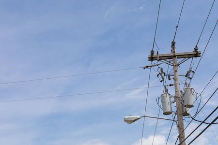 Wooden power pole with mixed power and fiber optics cable wires, street light and transformers against a blue sky with wispy clouds, horizontal aspect