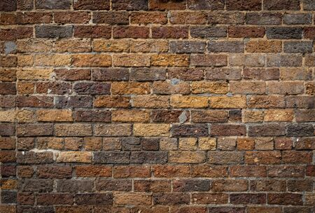 Mixed rustic brick background, rough texture backdrop in shades of brown and yellow ochre, creative copy space, horizontal aspect