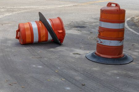 Two orange and white traffic safety barrels, one knocked over, metaphor for driving safety, danger and accidents, horizontal aspect