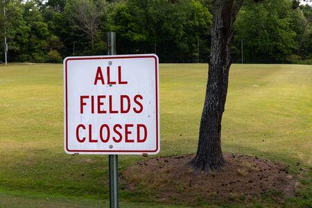 Empty green grass sports field behind a sign saying All Fields Closed, sports cessation due to coronavirus, horizontal aspect Stok Fotoğraf