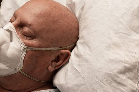 Head of a man with oxygen lines and respirator asleep on a pillow, bald cancer chemotherapy with coronavirus, horizontal aspect