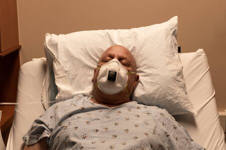Old bald man in a respirator in a hospital bed asleep on a pillow, coronavirus, cancer, chemotherapy, horizontal aspect Standard-Bild