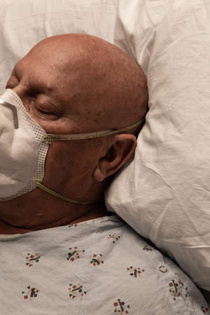 Head of a man wearing a respirator in a hospital bed, bald cancer chemotherapy, sick and dying, vertical aspect