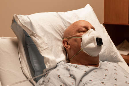 Head of a man in a hospital bed wearing a respirator and oxygen line, bald cancer chemo coronavirus, sick and asleep, horizontal aspect