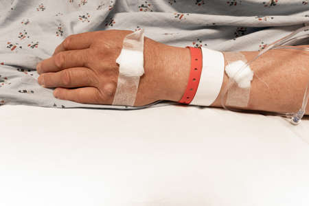 Wrist and hand of a man in a hospital bed, bandages, wristbands, IV lines, white sheet copy space medical healthcare background, horizontal aspect