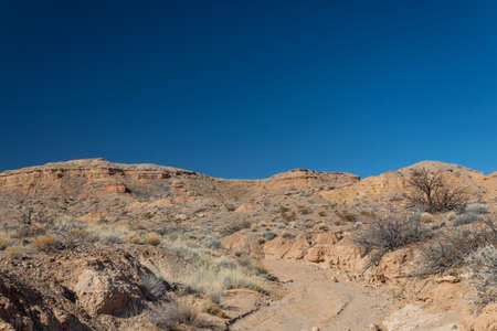 Wide path through the New Mexico desert leading up to a ridge before blue sky, road less traveled, horizontal aspect Stok Fotoğraf
