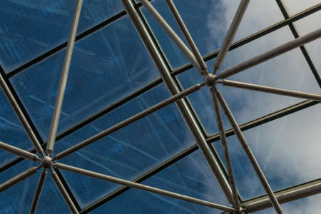 Elaborate steel metal greenhouse structure with diffuse view of deep blue sky with cloouds, horizontal aspect