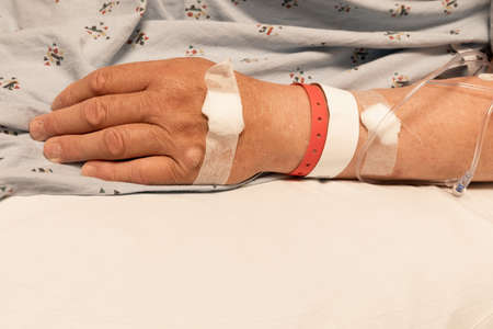 Close view of mans arm and hand with bandages and IV lines