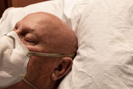 Head of a man wearing a respirator, asleep on hospital pillow Foto de archivo
