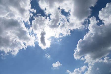View directly overhead of sun peaking through white and gray clouds, blue sky beyond, creative bbackground copy space, horizontal aspect