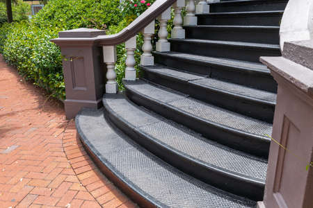 Sweeping exterior staircase with black cast iron treads leading to a brick sidewalk in a herringbone pattern, horizontal aspect 版權商用圖片