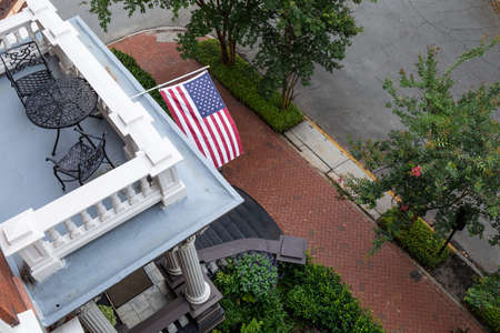 View looking down on balconies, stairs, sidewalk and street, American flag, horizontal aspect