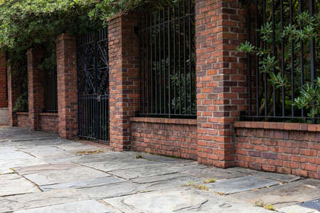 Tall brick and wrought iron wall beside a slate stone walkway, old architectural details, copy space, horizontal aspect