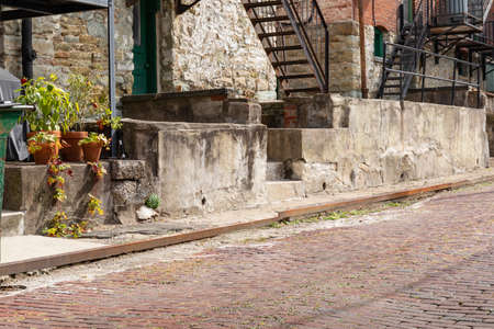 Red brick street with rusted metal curb edge, patched concrete retaining wall, metal stairs, horizontal aspect 版權商用圖片