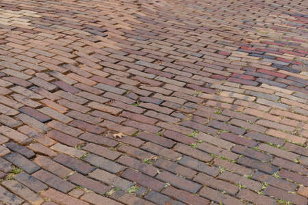 Mixed red brick roadway with grass growing in the cracks, running bond pattern background, horizontal aspect
