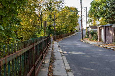Street and narrow sidewalk bordered by a rusted cast iron fence, garages, early fall urban landscape, horizontal aspect 版權商用圖片